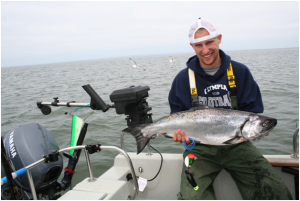 The author's downrigger gear includes a Silver Horde/Gold Star Rudder Flasher (hanging off the downrigger at left) and a size 000 Spin-n-Glo above the line-release clip. A Coho Killer fished with these added attractors fooled this 11-pound chinook for Dillon Reed of Olympia. (Terry Rudnick photo)