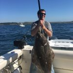Jason Schmidt does the lift and grin with a 58lb Halibut.