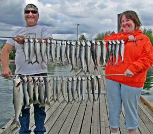 "Roberta ""big fish"" Iliff with Mike Chandler and Ron Wilson of Fairfield and Lincoln, WA with their catch of Lake Chelan Mackinaw and Cutthroat."